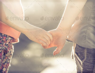 little girl and boy hold hands close-up, against the backdrop of a green garden.