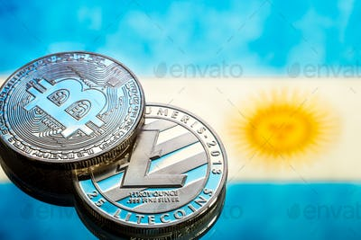 Coins Bitcoin and litecoin, against the background of Argentina flag.