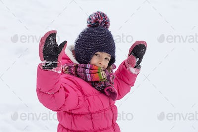 Warmly dressed little girl rejoices in the falling snow close up.