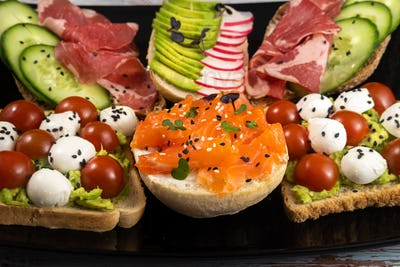 Assorted sandwiches with fish, cheese, meat and vegetables on a black plate and wooden background