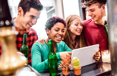 Multiracial milenial friends having fun with laptop at modern coworking space