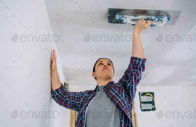 Bricklayer smoothing plaster ceiling with the trowel