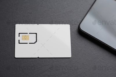 Blank white SIM card with smartphone on black slate. 3D rendering and photo