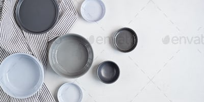 Banner with ceramic plates over light grey concrete background. Home cooking concept. Copy space