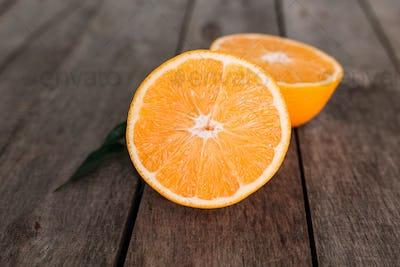 Halves of orange fruit on gray wooden background. Orange pulp and green leaves