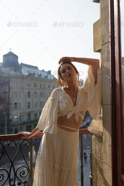 A young woman is resting on the balcony of her apartment overlooking the old town.