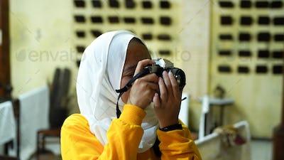 Asian women travel to see batik wearing jilbab and analog camera