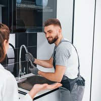 Young professional plumber in grey uniform shows results of work for housewife on the kitchen