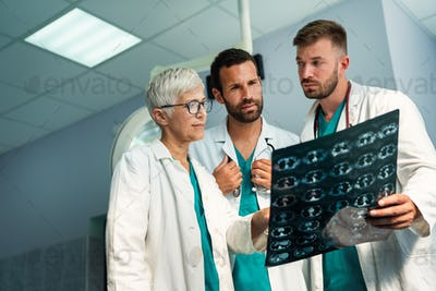 Group of radiology doctor looking at x-ray and discussing it
