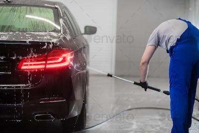 Worker at Car Wash Shop, Using Pressure Washer on Car, man washing car with a foam