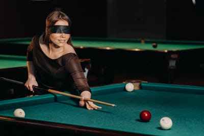 A girl with a blindfold and a cue in her hands in a billiard club.Russian billiards