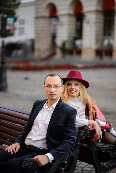 Adult married couple sits on a bench against the background of the old city.