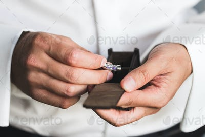 Preparations for the wedding, the groom wears cufflinks
