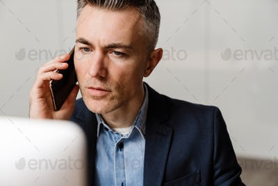 Focused grey man talking on mobile phone while working with computer