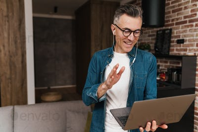 Happy man in earphones waving hand while taking video call on laptop