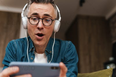 Surprised man in headphones using mobile phone while sitting on sofa