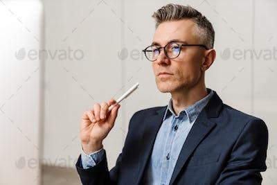 Thinking grey man wearing eyeglasses holding pen and looking forward