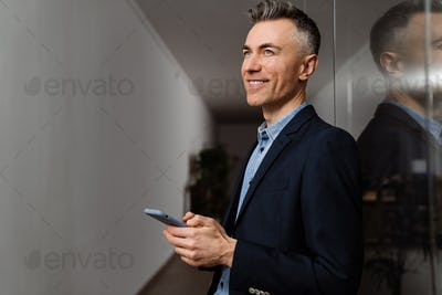 Smiling grey man using mobile phone while leaning on wall in office