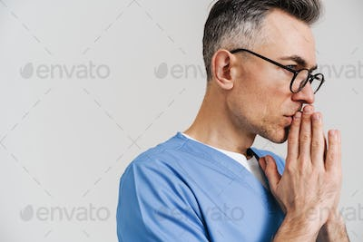 Tense white-haired medical doctor posing with palms together