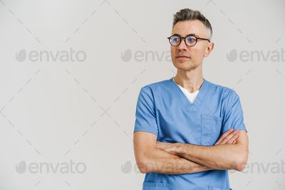 Happy white-haired medical doctor smiling and posing with arms crossed