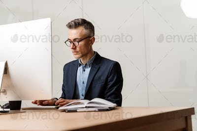 Focused grey man working with computer while sitting at table in office