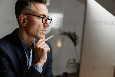 Thinking grey man working with computer while sitting at table in office