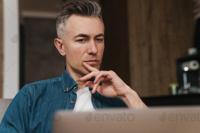 Focused handsome man using laptop while sitting on couch