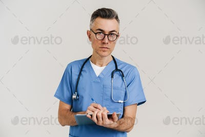 Focused grey doctor with stethoscope writing on medical file