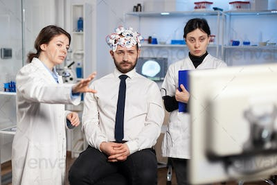 Neurological researchers explaning treatment result pointing on science monitor