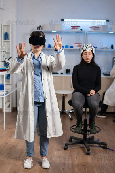 Neuroscience doctor gesturing wearing vr goggles in lab science