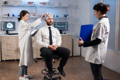 Ill man listening neurological doctor looking at clipboard