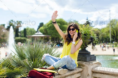 Excited girl in sunglasses is sitting on fence in summer park. She is speaking on phone and looking