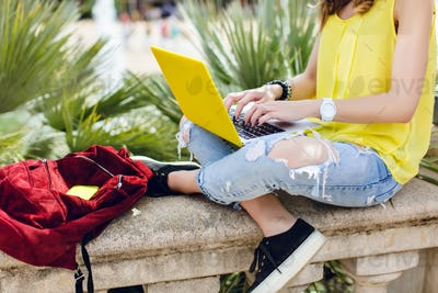 Yellow laptop on knees of a girl sitting on fence in park. She is typing on keyboard