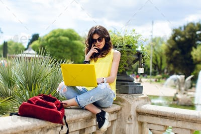 Brunette girl working with yellow laptop on summer in park. She is sitting on fence, looking busy