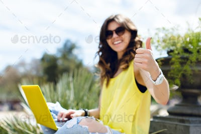 Focus on sign with hand of a girl in yellow T-shirt working with laptop in summer park