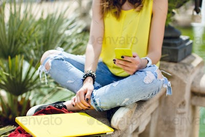 Yellow laptop, phone in hand of a girl in yellow T-shirt and jeans sitting on fence in summer park
