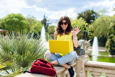 Brunette girl in sunglasses is sitting on fence in park. She holds yellow laptop and smiling to