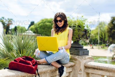 Pretty brunette girl is sitting on fence in park. She is busy at work on yellow laptop