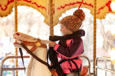 A little girl rides on a carousel, winter holidays.
