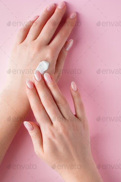 Woman is applying cream to her hands on pink background.