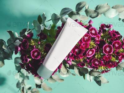 White generic cream tube on botanical background with pink flowers