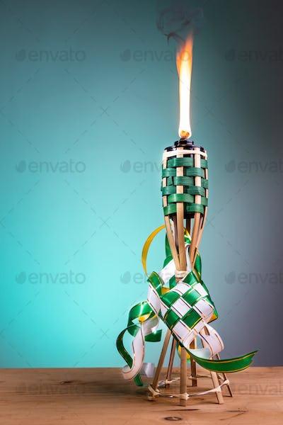 Traditional Malay torch and decorative ketupat lit up during Hari Raya Aidilfitri celebration