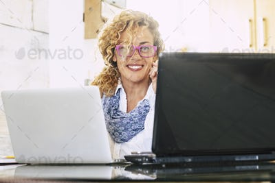 Beautiful blonde curly adul twoman wotk at the office with two laptop notebook at the same time