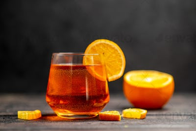 Front close view of fresh delicious juice in a glass with orange limes on dark background