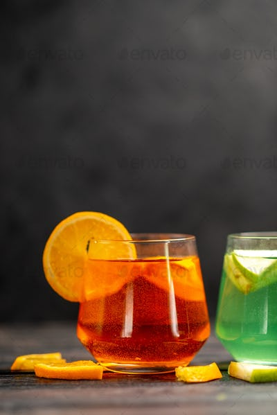 Vertical view of fresh natural delicious juice in two glasses with fruit limes on black background