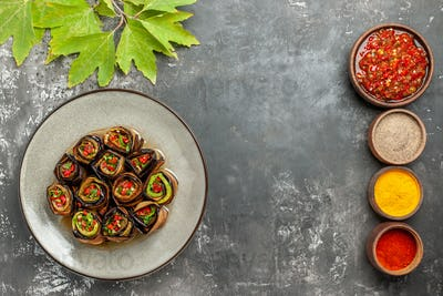 top view stuffed eggplant rolls in white plate different spices adjika in small bowls on grey