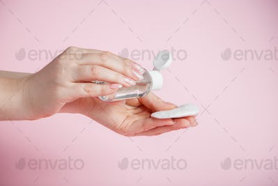 Hands of a young woman on pink background. Skin care
