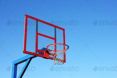 Basketball hoop on clear blue sky.