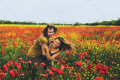Young happy couple with curly hair enjoying in bright red and yellow blossoming field of poppies