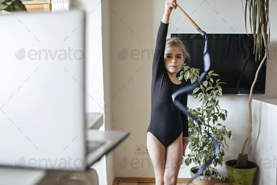 Girl in sportswear watching sport competition online and repeating exercises in rhythmic gymnastics